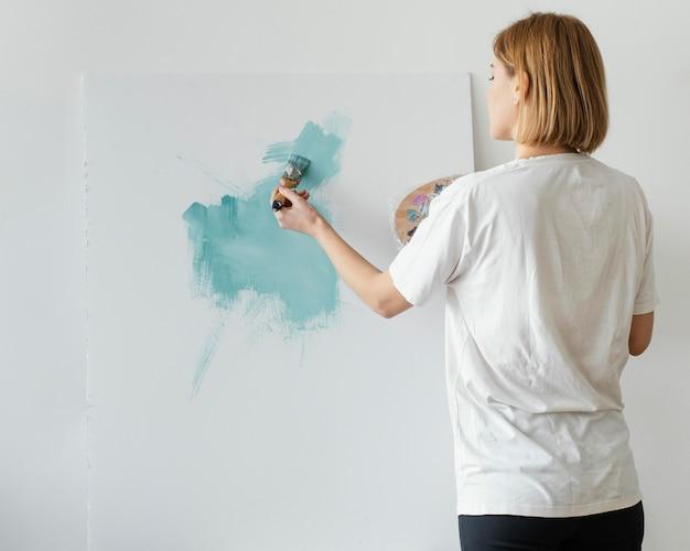 Młoda kobieta maluje akryle na płótnie
