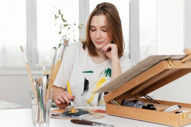 Młoda kobieta maluje akrylem