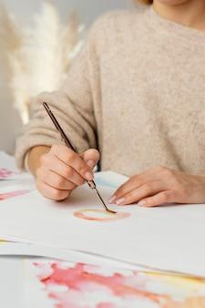 Młoda kobieta maluje akwarelami na papierze