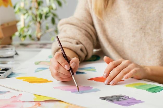 Młoda kobieta maluje akwarelami