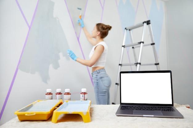 Młoda kobieta maluje ścianę wałkiem do malowania i używa laptopa z taśmą maskującą stojącego na stole z przodu