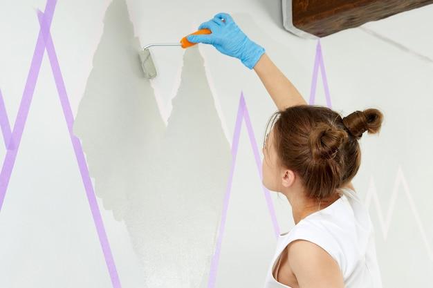 Młoda kobieta maluje ścianę wałkiem do malowania i używa taśmy maskującej stojąc na drabinie