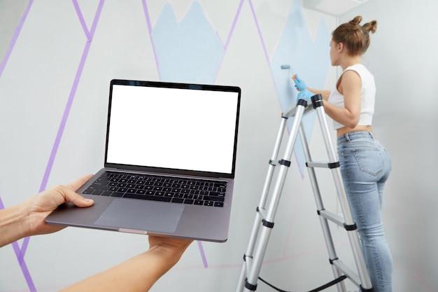 Młoda kobieta maluje ścianę za pomocą wałka do malowania i używa taśmy maskującej stojącej drabiny pn trzymającej rękę