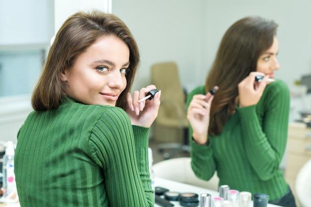 Młoda kobieta maluje usta w kolorze beżowym