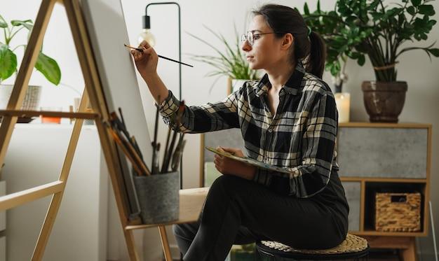 Młoda kobieta maluje w swoim mieszkaniu farbami olejnymi. studentka rysuje w studio sztuki. koncepcja badania sztuki. makieta płótna