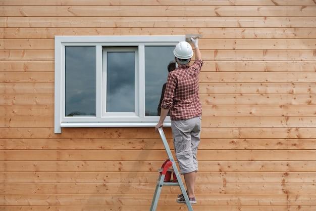 Młoda kobieta maluje zewnętrzną ścianę nowego drewnianego domu. proces malowania wiejskiego domu