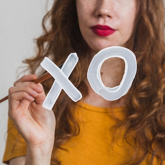 Młoda kobieta maluje znak xo