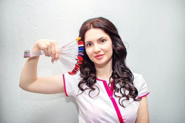 Młoda kobieta manikiurzystka pozuje z próbkami paznokci