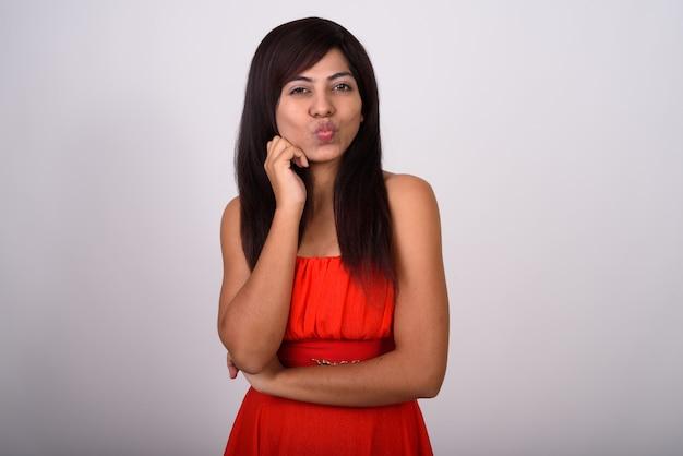 Młoda kobieta marszczy usta i gotowa do pocałunku, mając na sobie czerwoną sukienkę
