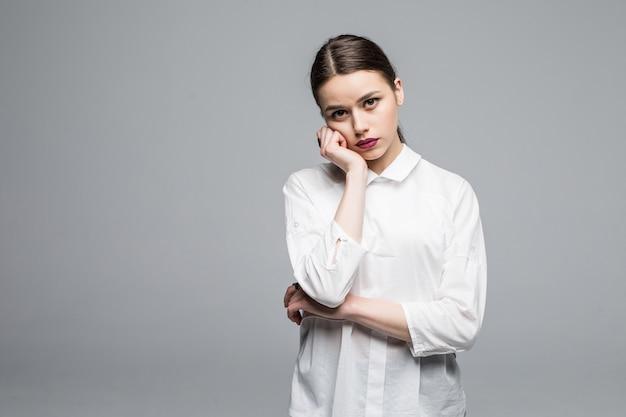 Młoda kobieta martwi się o przyszłość na białej ścianie