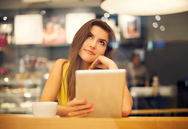 Młoda kobieta marzy w kawiarni