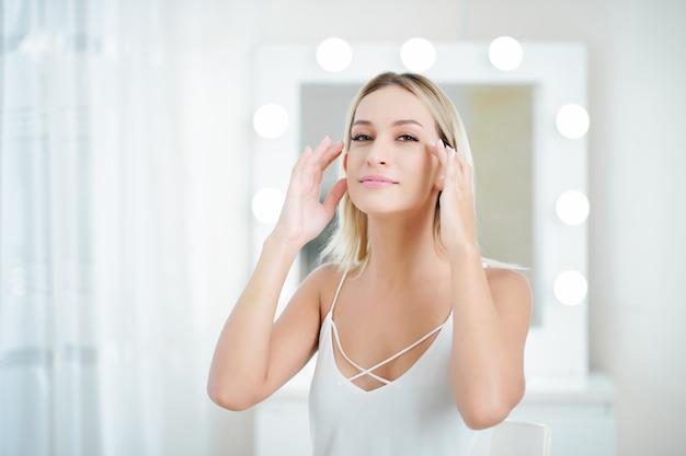 Młoda kobieta masuje twarz