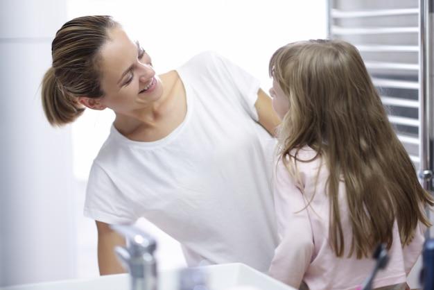 Młoda kobieta matka patrząc na dziecko i uśmiechając się w portret łazienka