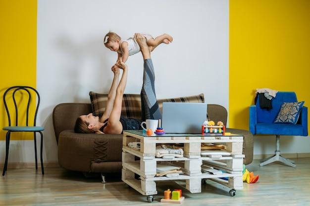Młoda kobieta matka siedzi na kanapie z córeczką w domu, oglądając ćwiczenia jogi