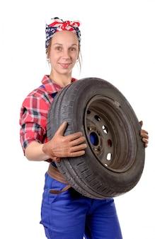 Młoda kobieta mechanik z samochodowym kołem