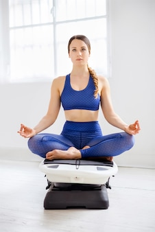 Młoda kobieta medytacji w pozycji lotosu na surfset w wysokiej siłowni klucz