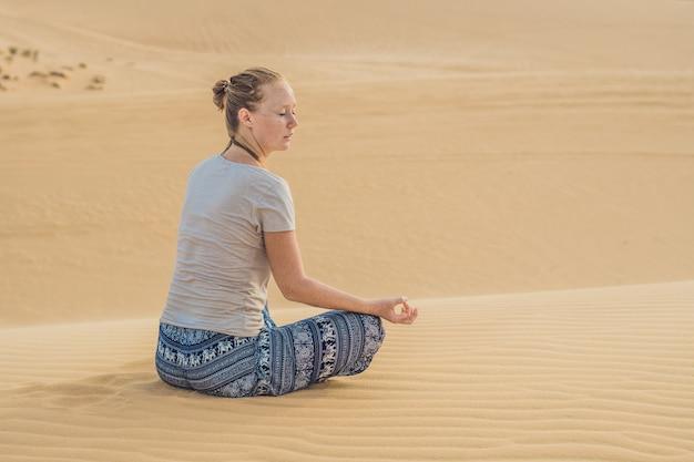 Młoda kobieta medytując na pustyni w wietnamie