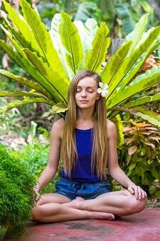 Młoda kobieta medytująca w ogrodzie z tropikalnymi roślinami