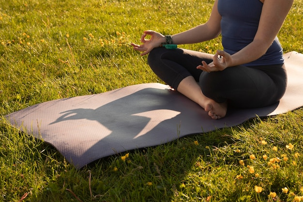 Młoda kobieta medytuje na zewnątrz na macie do jogi