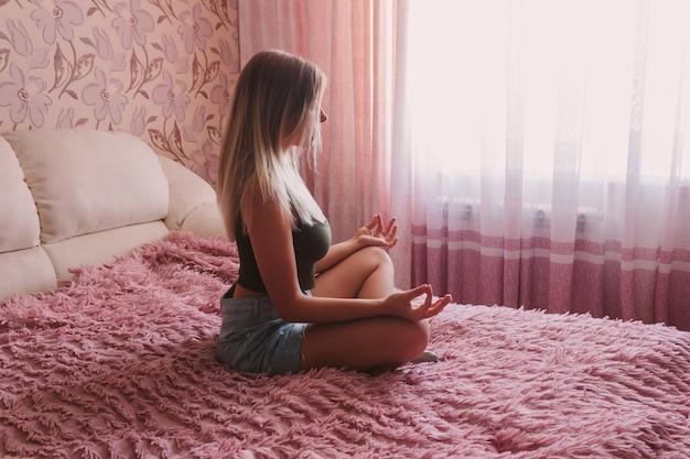 Młoda kobieta medytuje trzymając palce w znaku jogi z zamkniętymi oczami, siedząc na łóżku