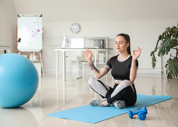 Młoda kobieta medytuje w biurze