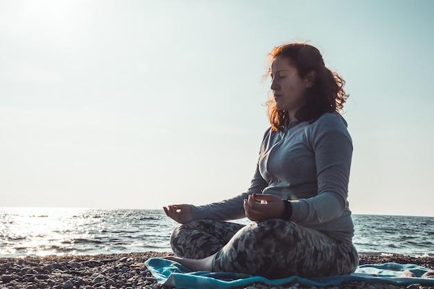 Młoda kobieta medytuje w brzeg