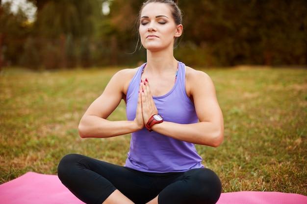 Młoda kobieta medytuje w parku. joga to ćwiczenie, które poprawia samopoczucie