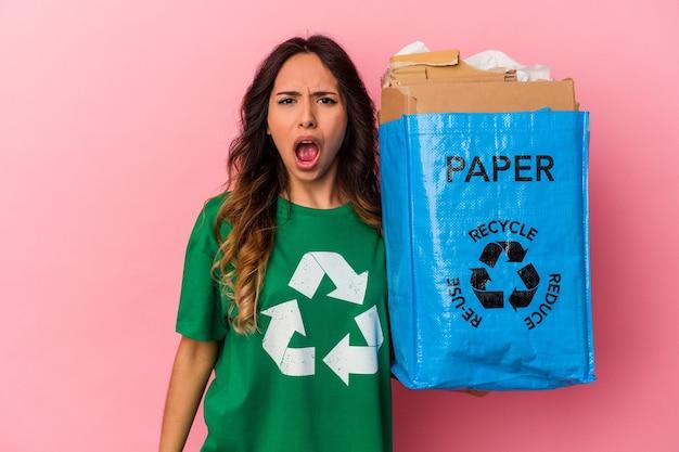 Młoda kobieta meksykańska recykling kartonu na białym tle na różowym tle krzyczy bardzo zły i agresywny.
