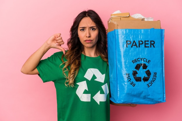Młoda kobieta meksykańska recykling kartonu na białym tle na różowym tle, pokazując gest niechęci, kciuk w dół. pojęcie sporu.