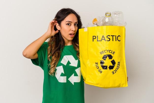 Młoda kobieta meksykański recyklingu tworzyw sztucznych na białym tle próbuje słuchać plotek.