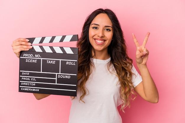 Młoda kobieta meksykańskie gospodarstwa clapperboard na białym tle na różowym tle wyświetlono numer dwa palcami.