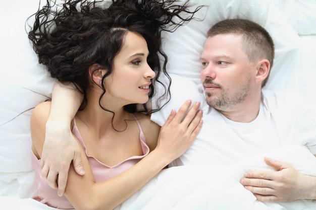 Młoda kobieta mężczyzna leży w łóżku i patrzy na siebie czule