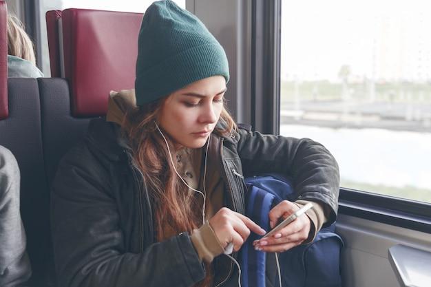Młoda kobieta miejska korzystająca z aplikacji telefonu i słuchawek bezprzewodowych do słuchania muzyki lub grania w gry online.