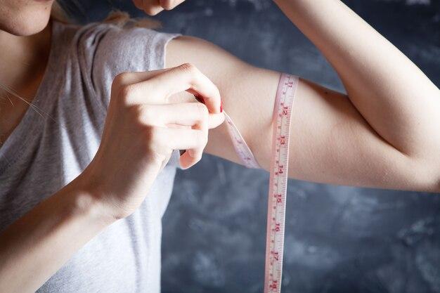 Młoda kobieta mierzy biceps taśmą mierniczą na szaro