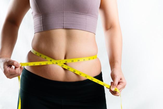 Młoda kobieta mierzy jej nadmiernego brzucha grubą talię z miarą taśmy, kobiety diety stylu życia pojęcie