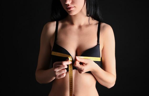 Młoda kobieta mierzy jej pierś w ciemności