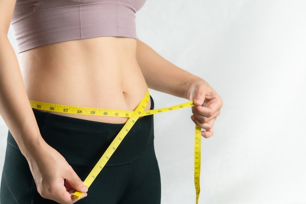 Młoda kobieta mierzy jej talię brzucha taśmą mierniczą, pojęcie diety kobiety