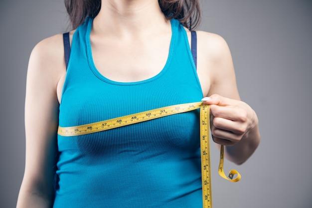 Młoda kobieta mierzy swój biust miarką