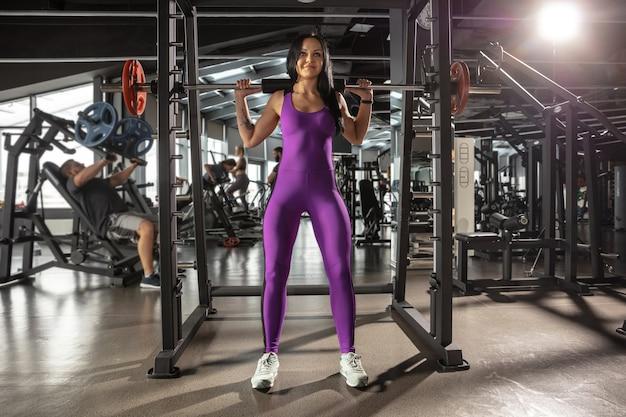 Młoda Kobieta Mięśni ćwiczenia W Siłowni Z Wyposażeniem Darmowe Zdjęcia