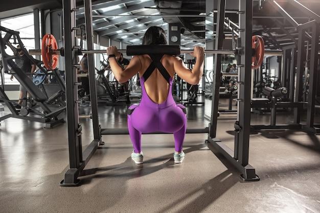 Młoda kobieta mięśni ćwiczenia w siłowni z wyposażeniem