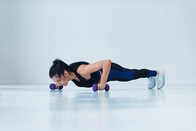 Młoda kobieta mięśni robi pushup ćwiczenia z hantlami na ciężki trening na siłowni
