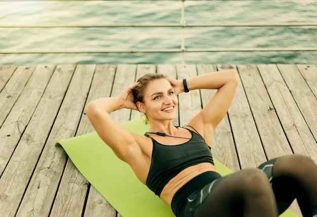 Młoda kobieta mięśni w odzieży sportowej wykonywania jej ciała z ćwiczeń skręcania mięśni brzucha, leżąc na macie na tarasie plaży