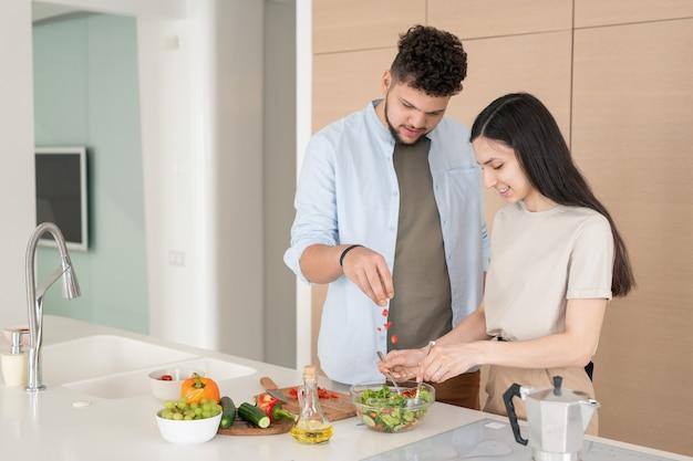 Młoda kobieta miesza składniki sałatki w misce, podczas gdy jej mąż dodaje pokrojone warzywa