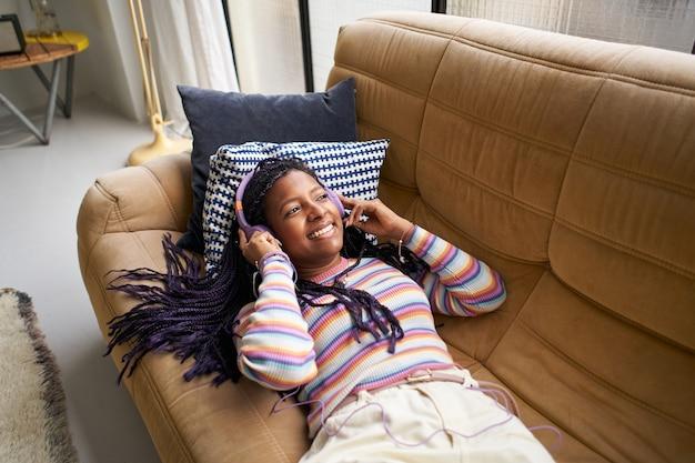 Młoda kobieta mieszana leżąca na kanapie słuchająca muzyki przez słuchawki