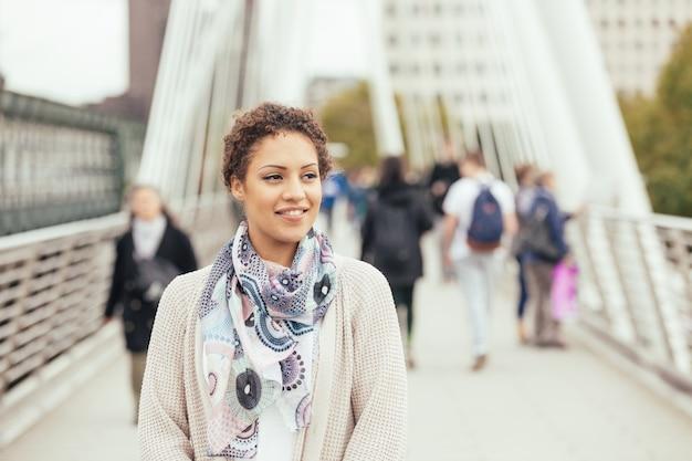 Młoda kobieta mieszanej rasy chodzenie na moście w londynie