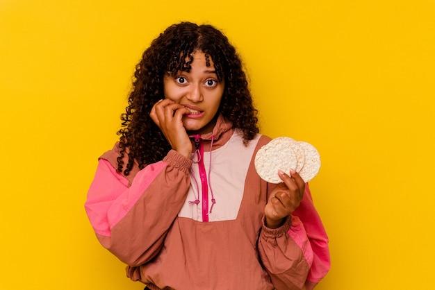 Młoda kobieta mieszanej rasy sportowej trzyma ciastka ryżowe odizolowane na żółtych paznokciach gryzących, nerwowa i bardzo niespokojna.