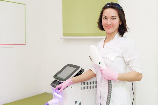 Młoda kobieta mistrzyni depilacji laserowej, rozstawiona laserem, uśmiechnięta kobieta. depilacja z sekcji kosmetycznej
