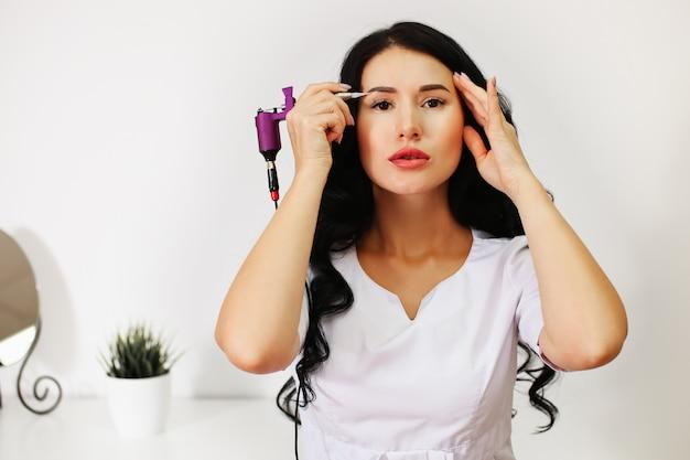 Młoda kobieta, mistrzyni makijażu permanentnego, brwi, powiek i kępek warg, opowiada pacjentce o przebiegu zabiegu