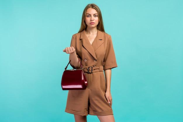 Młoda kobieta moda trzymać sprzęgło torebka na białym tle na niebieskim tle - obraz