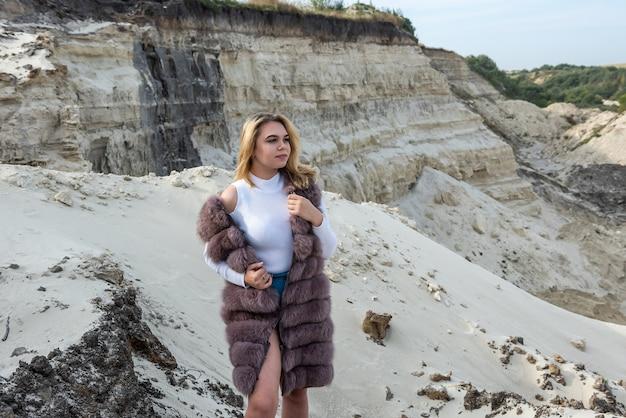 Młoda kobieta moda w futra pozowanie na piaszczystych skałach
